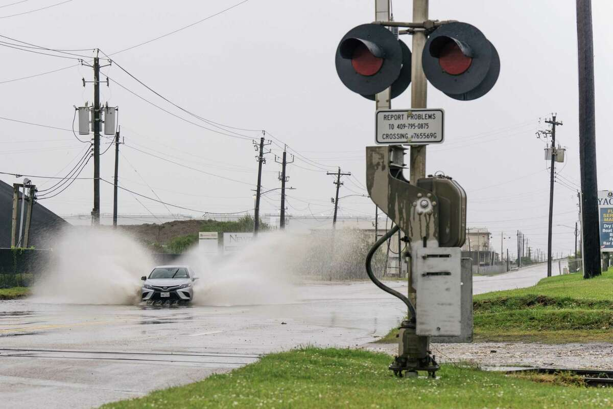 GALVESTON, TEXAS - SEPTEMBER 13: A car speeds through a flooded street ahead of the Tropical Storm Nicholas on September 13, 2021 in Galveston, Texas. A hurricane watch is in effect as Tropical Storm Nicholas is expected to make landfall later this evening. Parts of the Texas Gulf Coast, southwestern Louisiana, and Mexico may see up to 20 inches of rain with Nicholas bringing life-threatening storm surges, isolated tornadoes and projected tropical-storm winds of up to 115mph. (Photo by Brandon Bell/Getty Images)