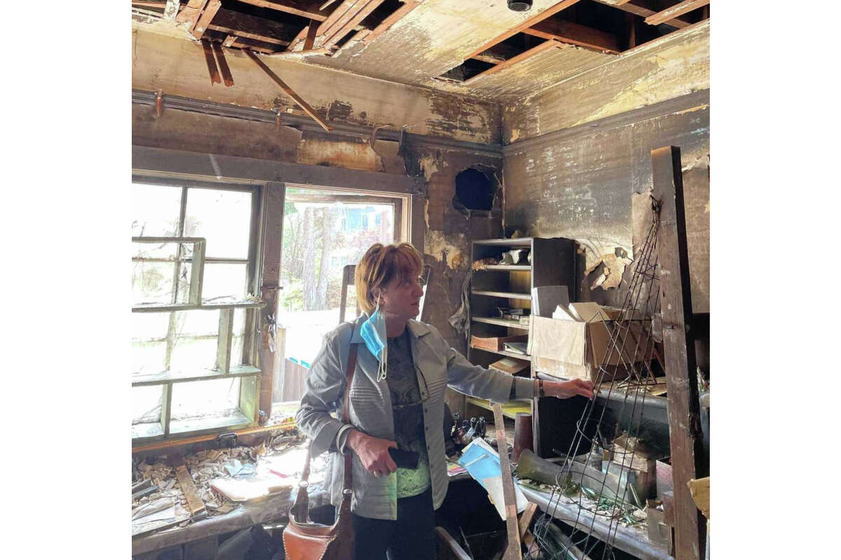 Sona Pehlivanian, owner of Frank's Floral Shop, inspects her burned-out shop following a robbery and fire the same night.