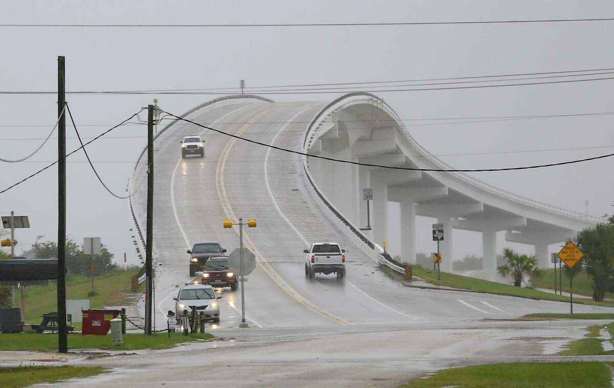 Vehicles make their way over the Intracoastal Waterway Bridge in Matagorda, Texas as Tropical Storm Nicholas approaches on Monday, Sept. 13, 2021. (Elizabeth Conley/Houston Chronicle via AP)