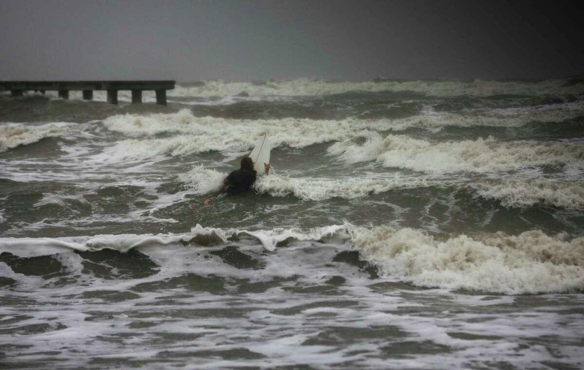 Un surfista intenta remar entre las olas mientras el viento y la lluvia de la tormenta tropical Nicholas golpea la zona, el lunes 13 de septiembre de 2021, junto al dique en Galveston, Texas. (Jon Shapley/Houston Chronicle via AP)
