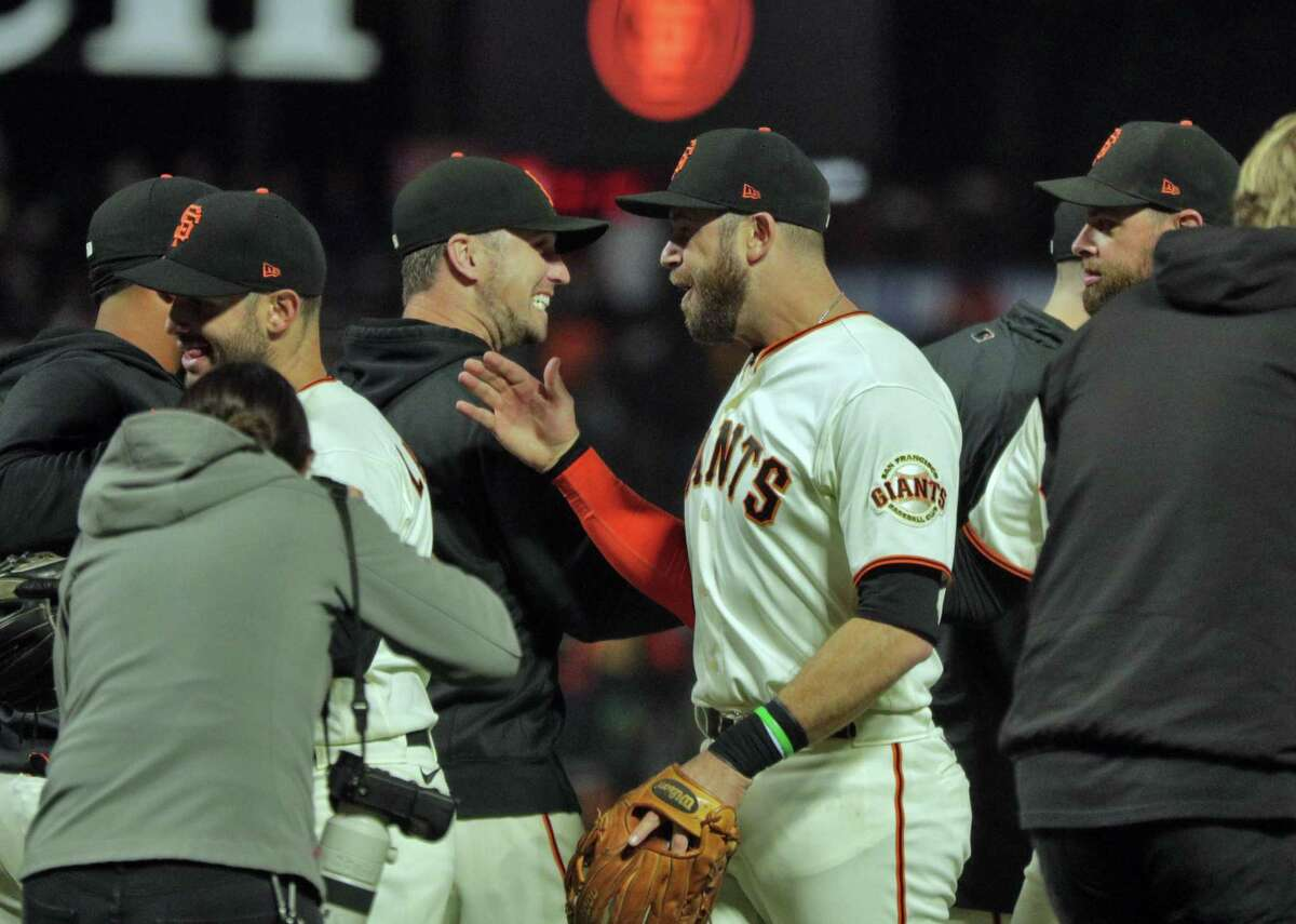 The San Francisco Giants celebrate after defeating the San Diego Padres 9-1 to clinch a playoff berth at Oracle Park in San Francisco.