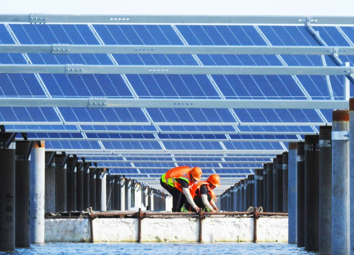 Workers install solar panels at a fishery-solar hybrid power station on September 14, 2021 in Lianyungang, Jiangsu Province of China. (Photo by Geng Yuhe/VCG via Getty Images)