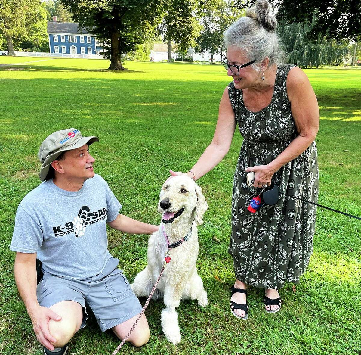 Dan Montuori with Stella and a fan, Debbie Longyear, walking her Shih Tzu, Acacia, on the Madison green.