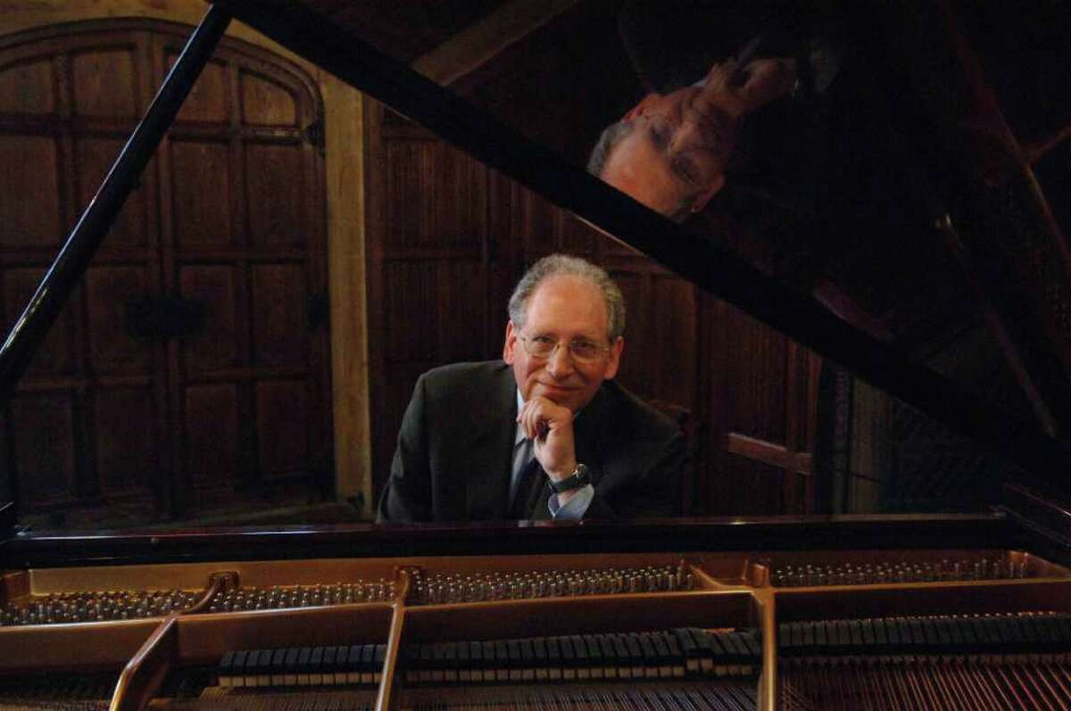 Pianist Orin Grossman, former academic vice president at Fairfield University, sits at the piano in the Great Room at the university's Bellarmine Hall. Grossman will present a concert of Chopin and Albeniz Sept. 25 at 8 p.m. at the Quick Center for the Arts at Fairfield University.