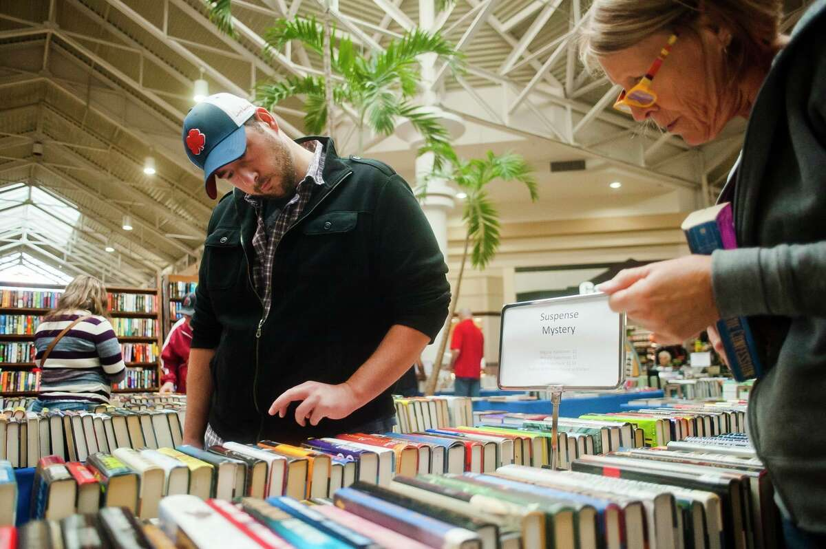 Visitors peruse books in the suspense/mystery section during a previous AAUW book sale. (File photo/Midland Daily News)