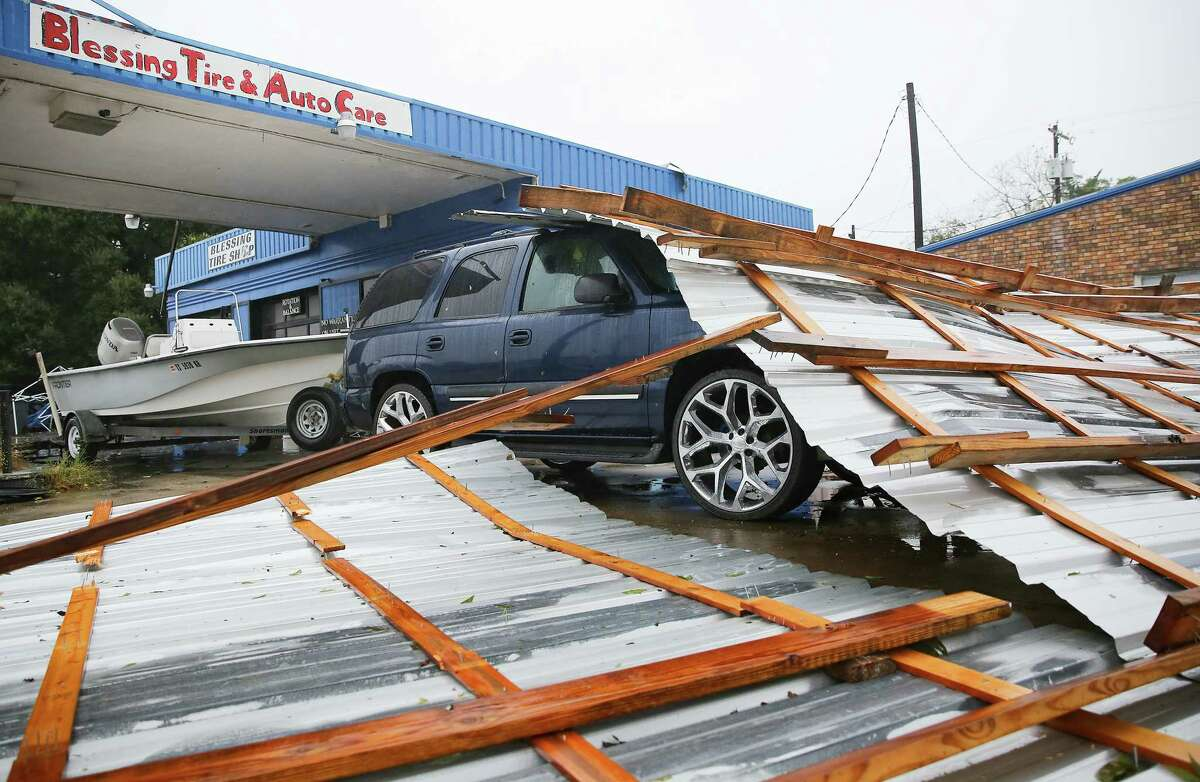 A roof on top of a car parked at Blessings Tire and Auto Care following Hurricane Nicholas in Bay City on Tuesday, Sept. 14, 2021. According to the owner of the business, he wasn't sure where the roof came from.