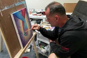 Artist John Zoccoli, who spent 25 years in prison on a robbery and murder conviction, works on a painting in the studio of his Albany apartment.