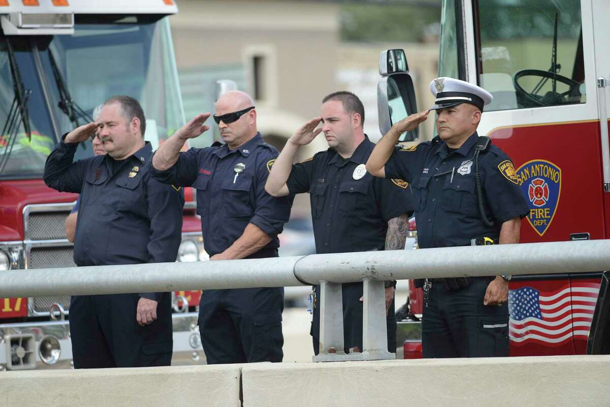 Police officer David Pantoja, right, joins firefighters atop the Henderson Pass overpass to pay respects to a fallen police officer on Sept. 2, 2014. Pantoja, a 24-year veteran of the force, received a 20-day suspension in July after officials said he he pulled a handcuffed suspect backward by his arms, injuring him.