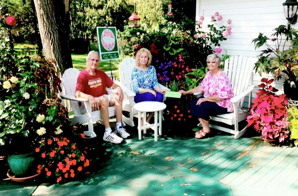 Mary Metzger, member of Spirit of the Woods Garden Club (right) recently honored Barry andMary Peterson as the September Garden of the Month. (Courtesy photo)