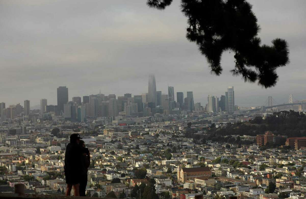 A couple looks at the San Francisco skyline in San Francisco, Calif. Following last week's showers, North Bay residents might see a few drops of rain over the weekend - but that forecast could quickly change, the National Weather Service said.