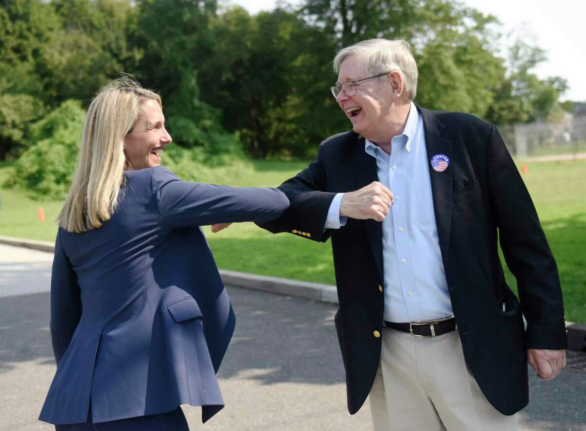 Mayoral candidate State Rep. Caroline Simmons and incumbent Mayor David Martin greet each other outside Dolan Middle School on Primary Election Day in Stamford, Conn. Tuesday, Sept. 14, 2021. Registered Democrats voted between incumbent Mayor David Martin and challenger State Rep. Caroline Simmons to choose who would face off against former Major League Baseball manager Bobby Valentine in the Stamford mayoral election in November.