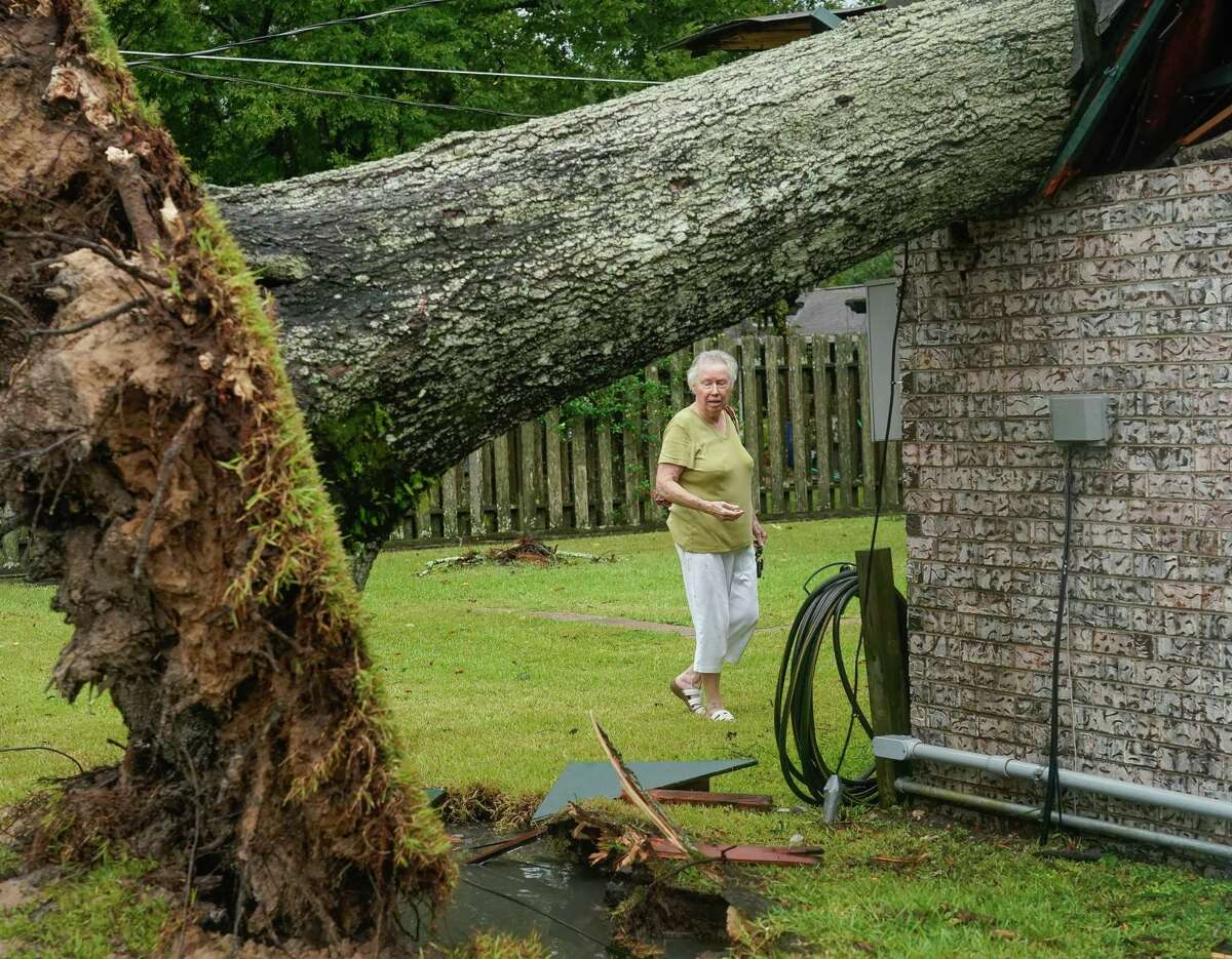 Marie Davis looks at the damage caused by a tree which was knocked over into her home during Tropical Storm Nicholas, on Tuesday, Sept. 14, 2021, in Baytown. This is the third time a tree has falle into Davis' home; hurricanes Alicia and Ike were the prior two occurrences.