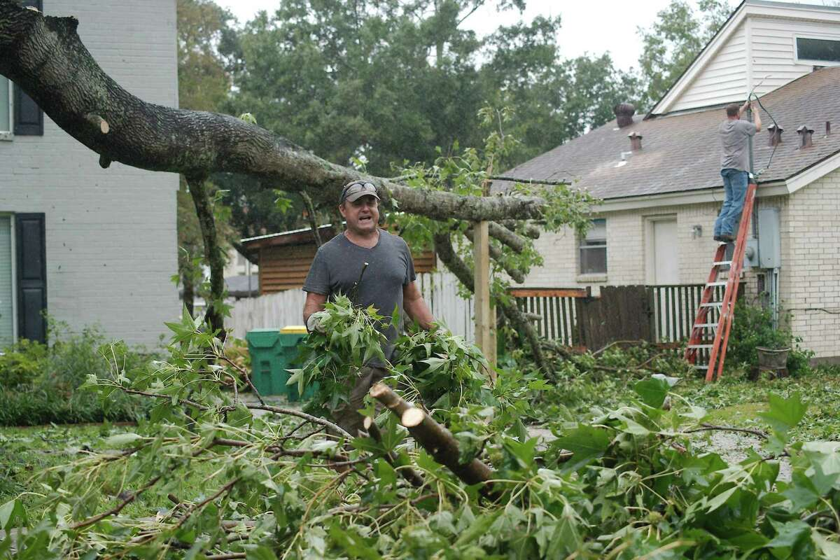 Seabrook resident Mike Lovfald cleans debris from his yard after a limb fell across his driveway, damaging his car and ripping power lines during Tropical Storm Nicholas.