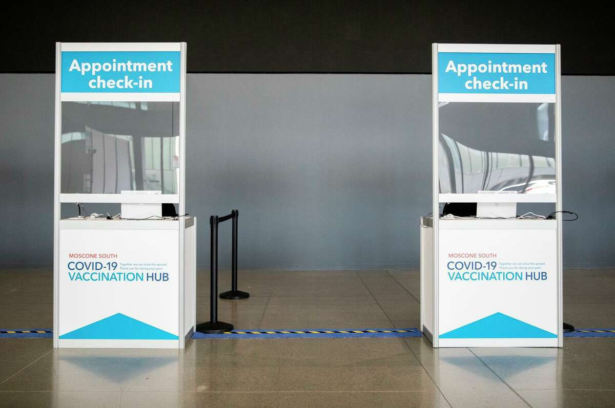 A row of COVID-19 vaccine check-in counters at Moscone South in San Francisco in February.