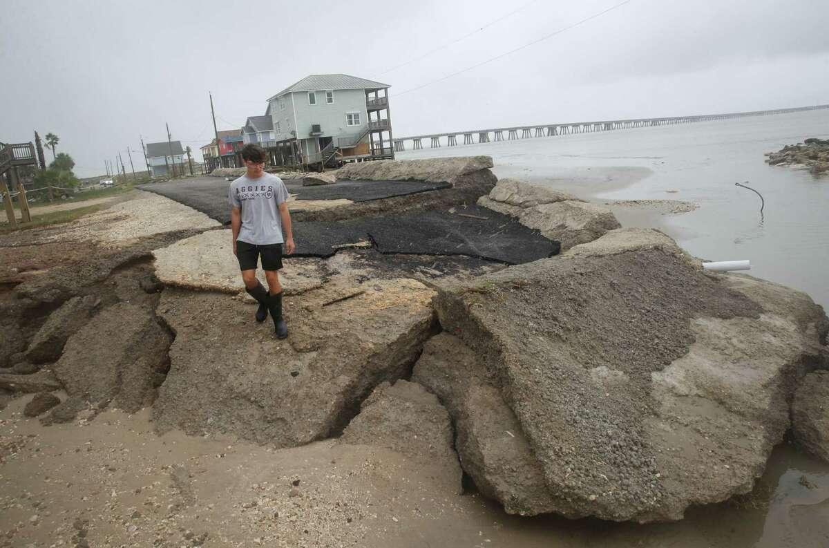 "Carson Coen, 17, surveys his neighborhood Tuesday, Sept. 14, 2021, in Treasure Island, a community at the San Luis Pass. Hurricane Nicholas made landfall down the coast early that morning. ""It felt a little apocalyptic,"" he said."
