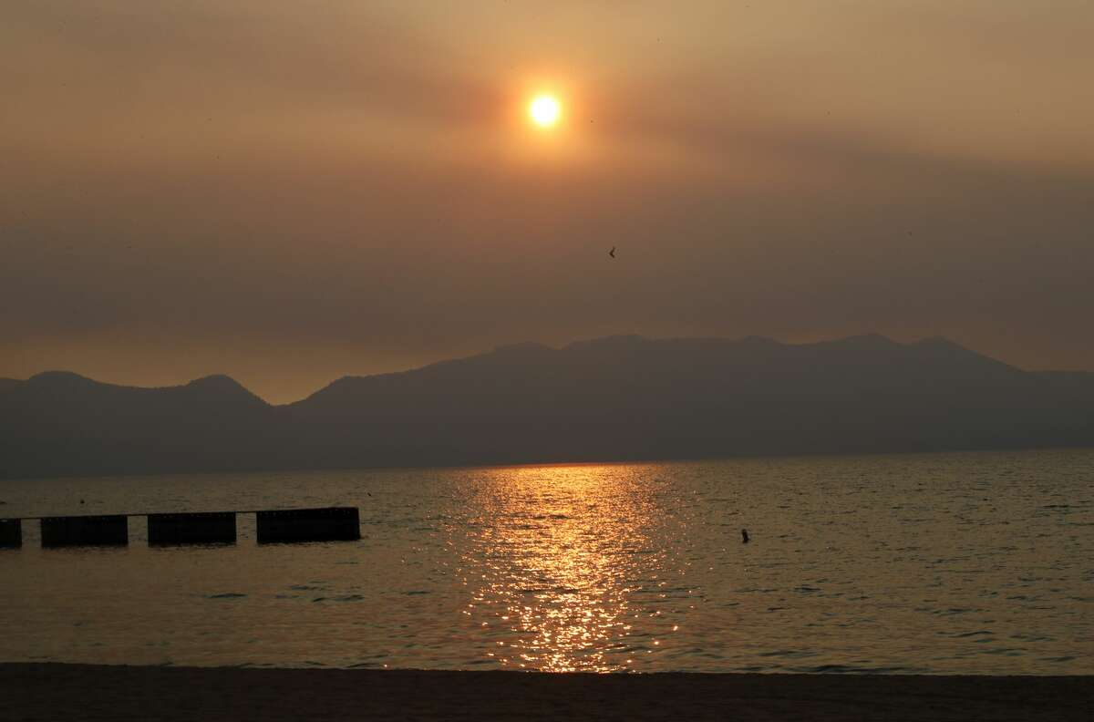 A smoky sunset is seen over Lake Tahoe in this view from Lakeside Beach in South Lake Tahoe, Calif., on Sunday, Sept. 6, 2021.