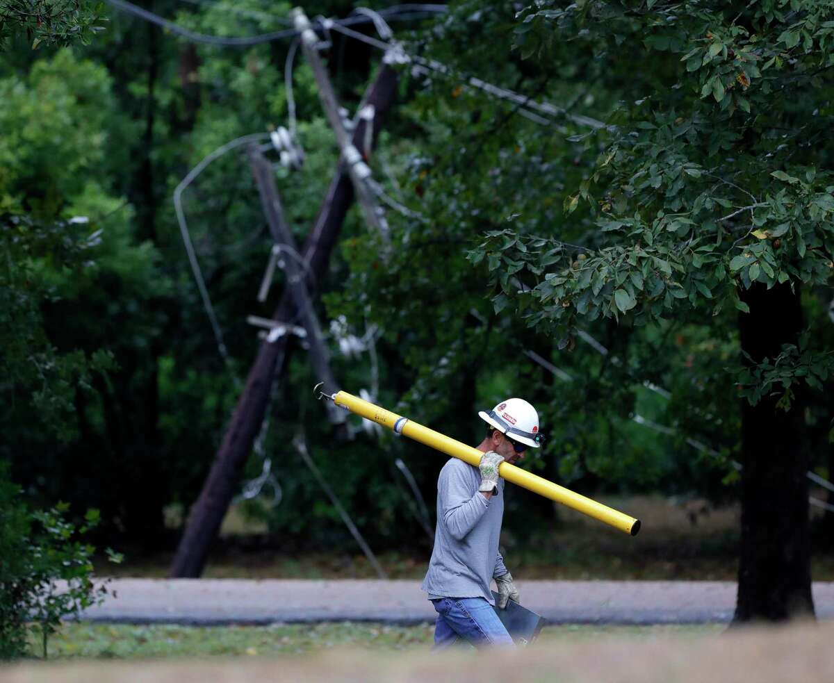 A worker with Entergy walks past a downed power line after trees on either side of Braxton Bragg Lane near River Plantation Drive in River Plantation fell overnight as Hurricane Nicholas moved through the region, Tuesday in Conroe.