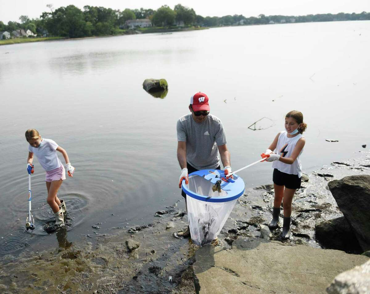 """Stamford's Michael Wirgin picks up trash with his daughters Zoe, left, 11, and Molly, 11, at Congregation Agudath Sholom's """"Reverse Tashlich"""" event at Gus Edson Park on Holly Pond in Stamford on Sunday. Tashlich is a Jewish tradition where congregants throw pebbles and bread crumbs into water to symbolically cast away sins before Yom Kippur. Congregation Agudath Sholom, however, does a reverse process where kids and adults remove trash and pollutants out of the water."""