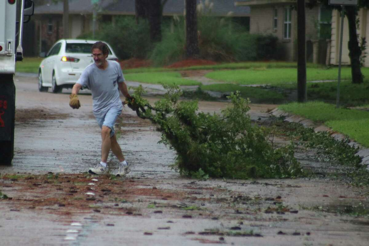 Greg Pfohl drags a tree limb from his front yard across the southbound lanes of Blackhawk Boulevard to a waiting Friendswood Public Works Department dump truck during cleanup after Tropical Storm Nicholas.