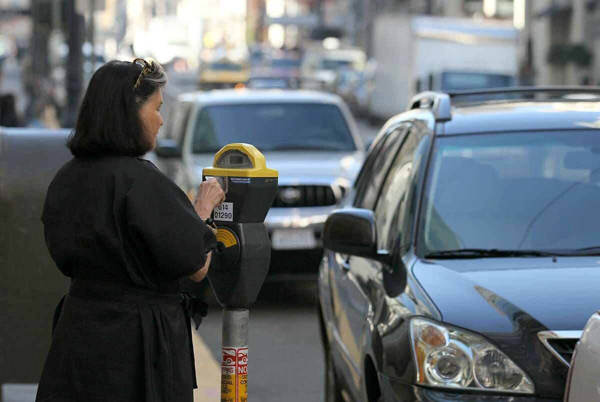 A woman puts money into a parking meter on January 21, 2011 in San Francisco.