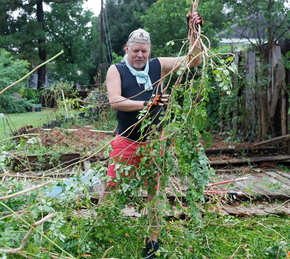 """Karl Gunderson works to remove brush and wood after wind from Tropical Storm Nicholas blew over the fence on east side of his home, Tuesday, Sept. 14, 2021, in Spring. """"It's really not that bad,"""" Gunderson said of the damage to his property. """"This storm could have been much worst."""""""