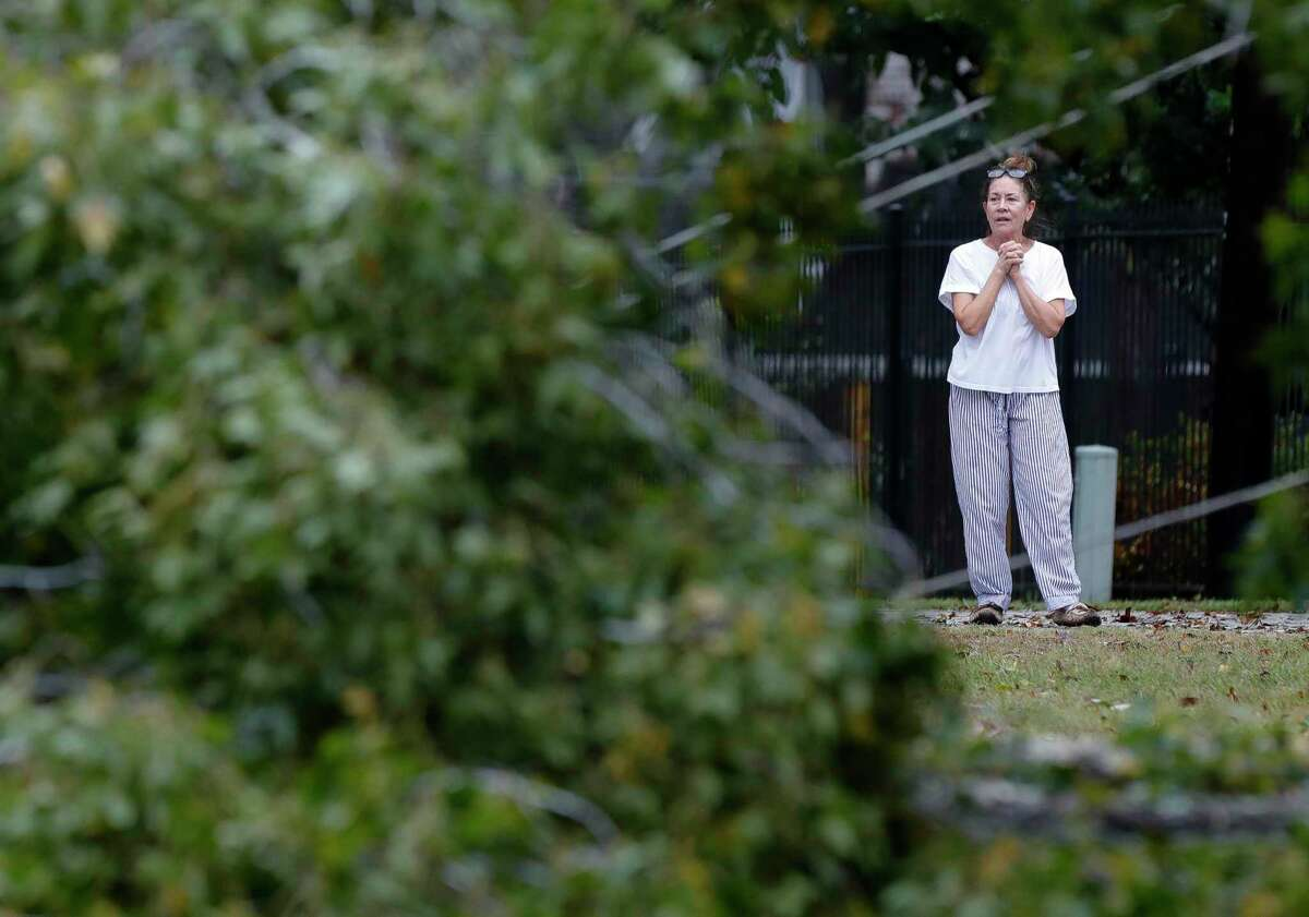 Fanny Poarch looks at a tree near her home along Braxton Bragg Lane in River Plantation that fell overnight, cutting off power to homes in River Plantation as Tropical Storm Nicholas moved through the region, Tuesday, Sept. 14, 2021, in Conroe.