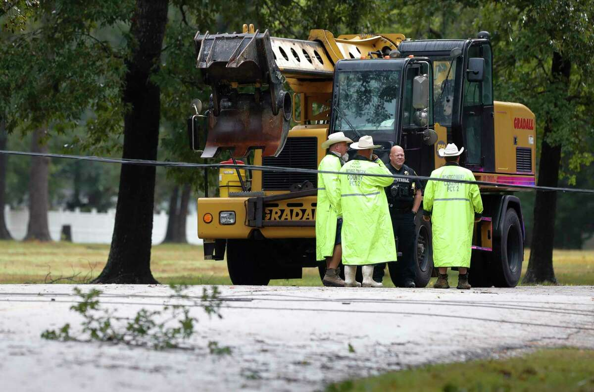 Crews with Montgomery County Precinct 2 work to remove a downed power line after trees on either side of Braxton Bragg Lane near River Plantation Drive in River Plantation fell overnight as Tropical Storm Nicholas moved through the region, Tuesday, Sept. 14, 2021, in Conroe.
