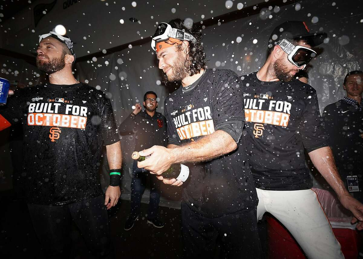 Brandon Crawford braces to pop open a bottle as the Giants celebrate in the clubhouse after clinching a playoff berth at Oracle Park in San Francisco, Calif., on Monday, September 13, 2021.
