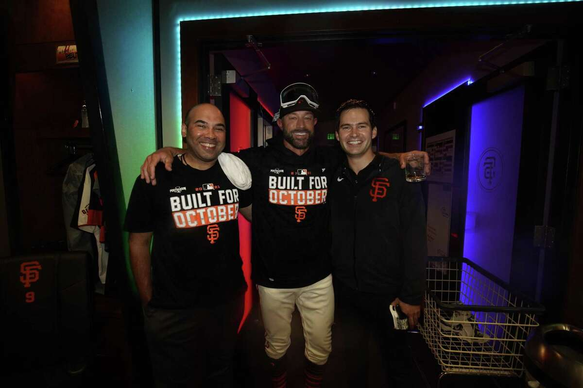 From left, Giants president of baseball operations Farhan Zaidi, manager Gabe Kapler and general manager Scott Harris pose for a photo after clinching a playoff berth at Oracle Park in San Francisco, Calif., on Monday, September 13, 2021.
