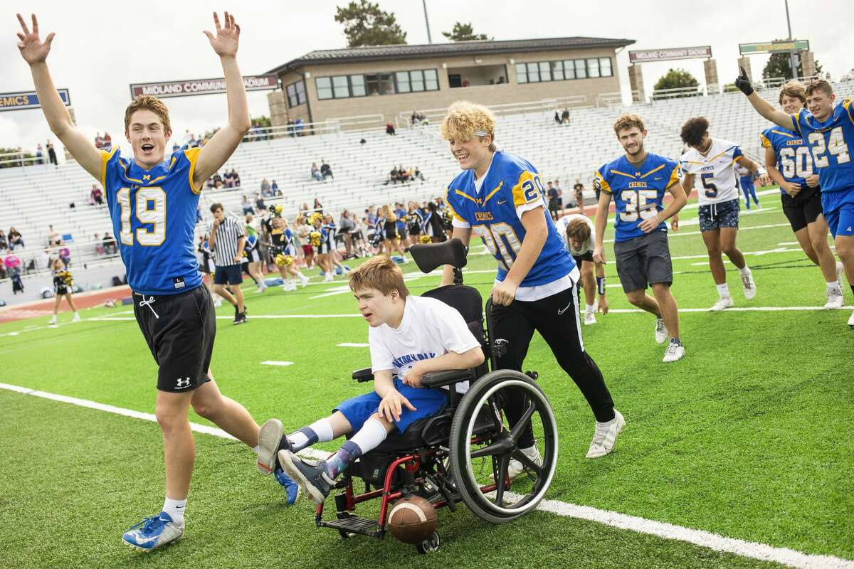 Drew Barrie, left, raises his hands into the air as Gabe Moline, center right, helps Nathan Fletcher, center, to score a touchdown during Victory Day, an event hosted by Midland High School that celebrates inclusion, teamwork and unity, Monday, Sept. 13, 2021 at Midland Community Stadium. (Katy Kildee/kkildee@mdn.net)