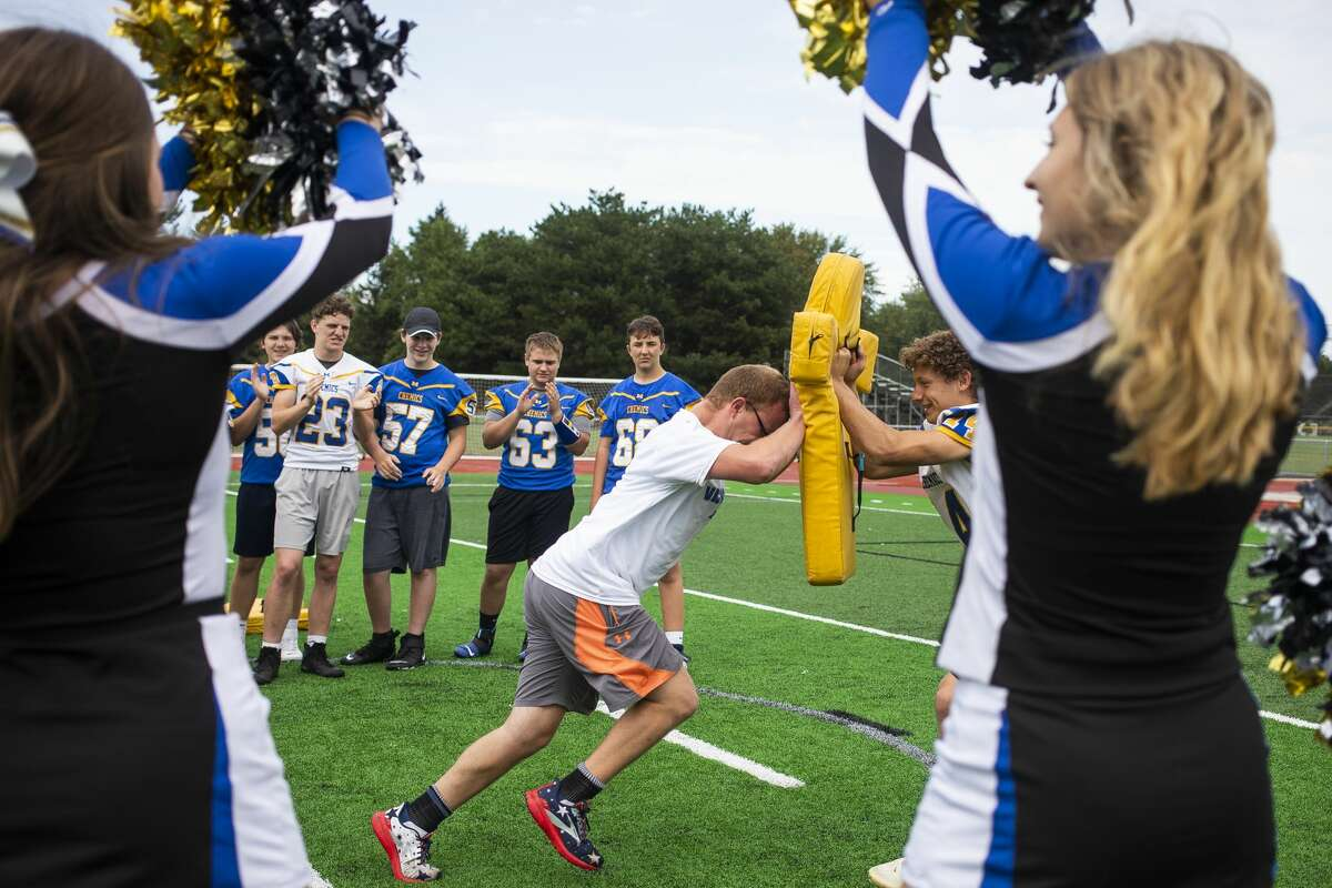 Midland High student Silas Pitt completes a drill with a football player during Victory Day, an event that celebrates inclusion, teamwork and unity, Monday, Sept. 13, 2021 at Midland Community Stadium. (Katy Kildee/kkildee@mdn.net)