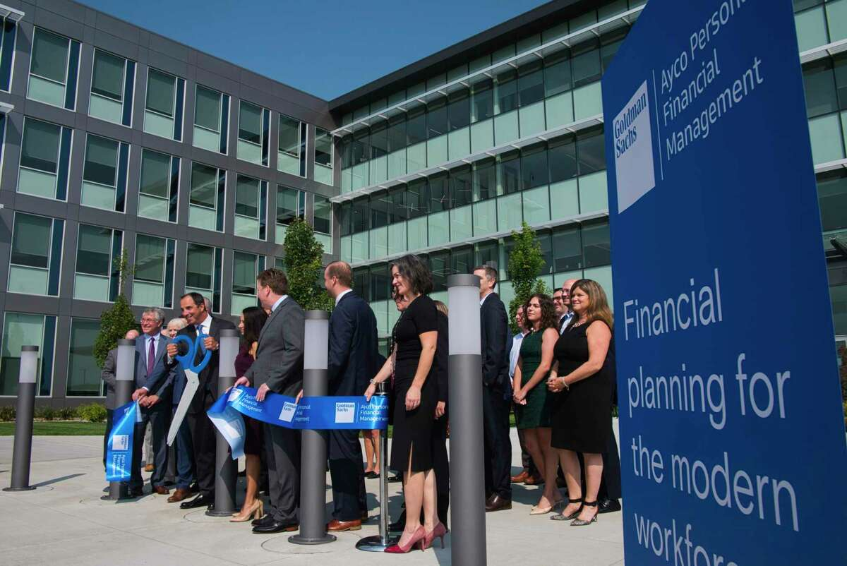 Larry Restieri, CEO of Goldman Sachs Ayco Personal Financial Management, uses large scissors to cut a ribbon outside the company's new headquarters on Tuesday, Sept. 14, 2021, in Cohoes, N.Y.