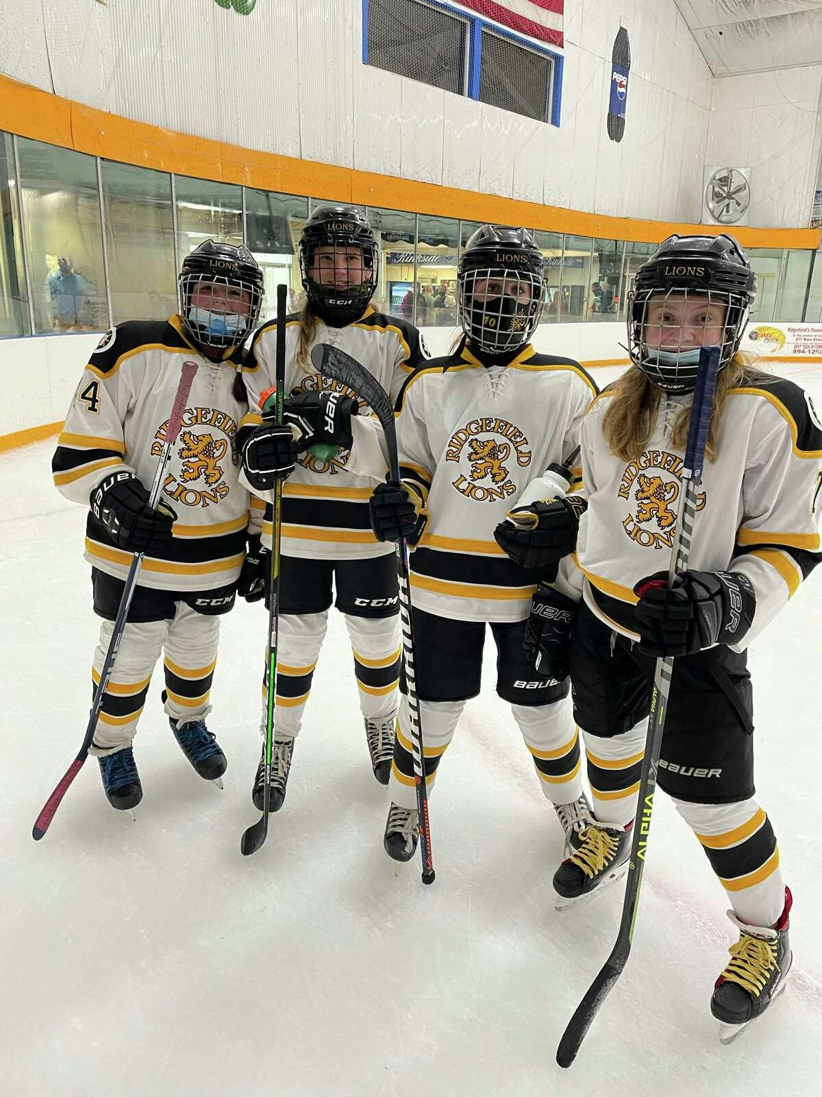 Ridgefielders Ava Jones, left, Lulu Presbrey Keira Brodovicz and Lexi Morse gear up at the Danbury Ice Arena. The Ridgefield Amateur Hockey Association has merged with the Danbury Hat Tricks to offer a veritable hockey home for children to grow up in.