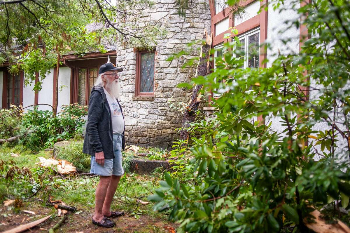 Midland resident Stacy Daniels looks at his damaged home on Sept. 13, 2021. His home was damaged from a lightning strike that hit some trees in his front yard.
