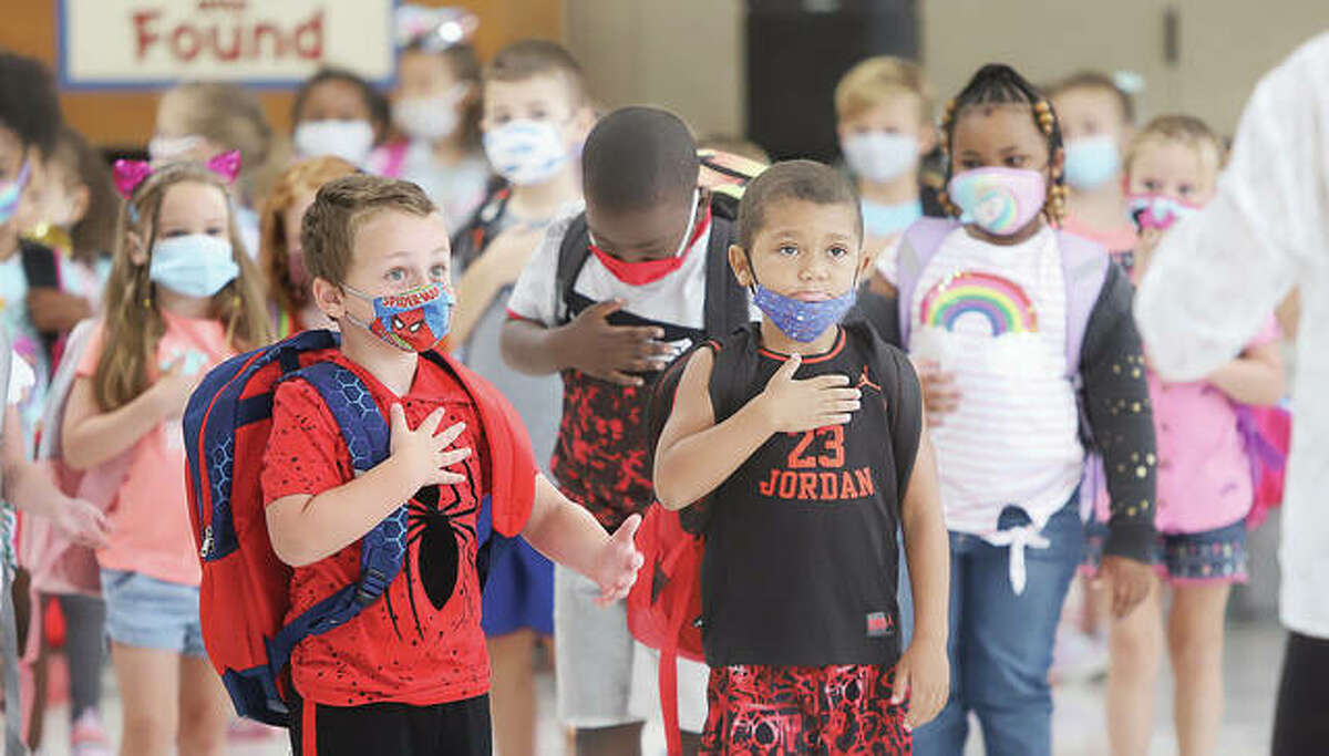 Students at Gilson Brown Elementary School in Godfrey place their hands over their hearts on Aug. 19, the first day of school this year in the Alton School District. On Tuesday legislative oversight panel said it wants the Illinois State Board of Education to adopt formal rules on how it will enforce its indoor mask mandate.