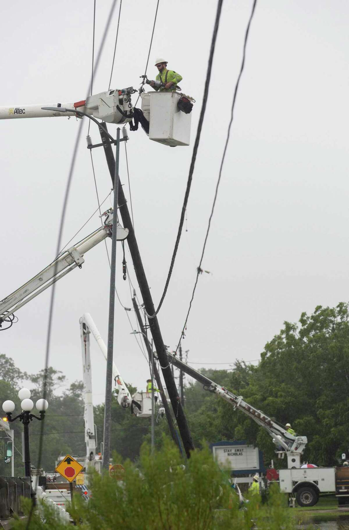 Workers repairing a downed power line on Clear Lake Road Tuesday, Sept. 14, 2021, in Clear Lake Shore, Texas. (Yi-Chin Lee/Houston Chronicle via AP)