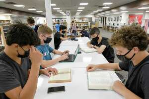 Freshman students, from left to right, Ryan Smith, Finian Hickey, Gordon Johns, and Tyler Selitte study in the media center on the first day of school at Cheshire High School, Tuesday, Aug. 31, 2021, in Cheshire, Conn.(Dave Zajac/Record-Journal via AP)