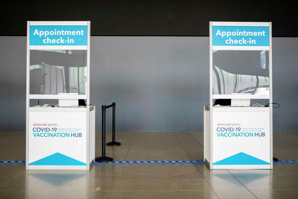 A row of check-in counters are seen on the main level of Moscone South as Kaiser Permanente and San Francisco staffers work to prepare a mass COVID-19 vaccination site at Moscone South in San Francisco, Calif.