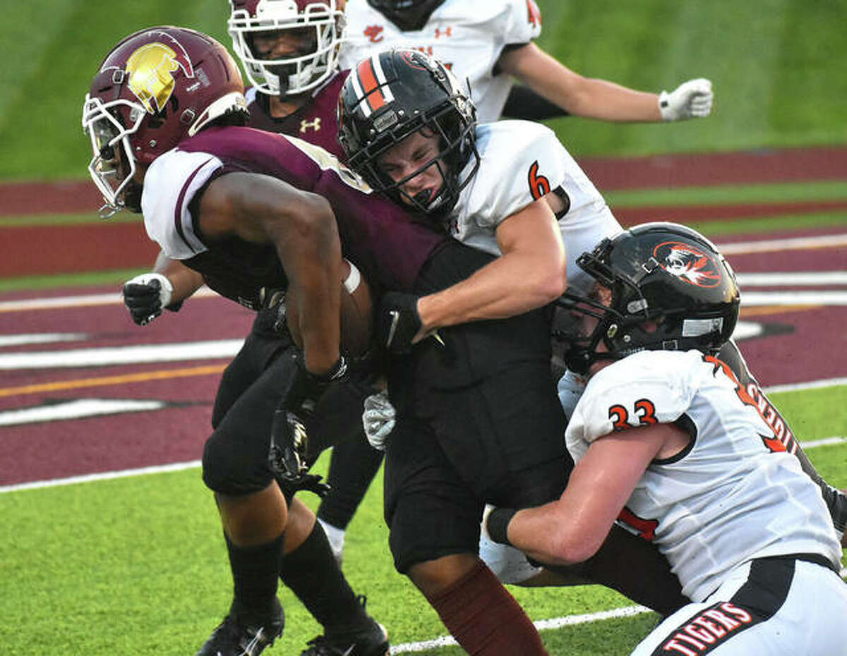 Edwardsville cornerback Carter Knoyle, top, and Dalton Brown, bottom, combine to make a tackle against De Smet during Week 1.