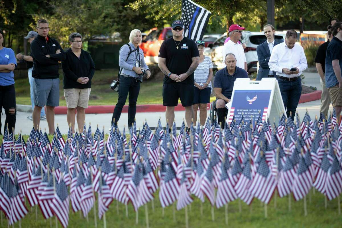 """Spectators look among a collection of U.S. flags as the names of first responders who lost their life during the 9/11 terrorist attacks during the Patriot Day of Remembrance at Central Fire Station, Saturday, Sept. 11, 2021, in The Woodlands. The ceremony included a Presentation of Colors by The Woodlands Fire Department Honor Guard along with a reading of """"The Fireman's Prayer"""" and """"The Ringing of the Bell"""" in honor of fallen firefighters."""