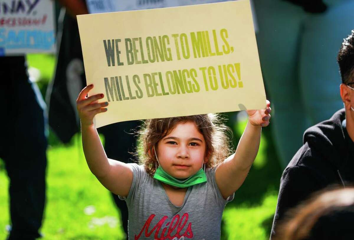 """Over objections of many alumnae, Mills College, a historic all-women's college, will merge with a private Boston university and become """"gender inclusive,"""" trustees decided. Claire Oyidiana holds up a protest sign when the college first announced its plans."""