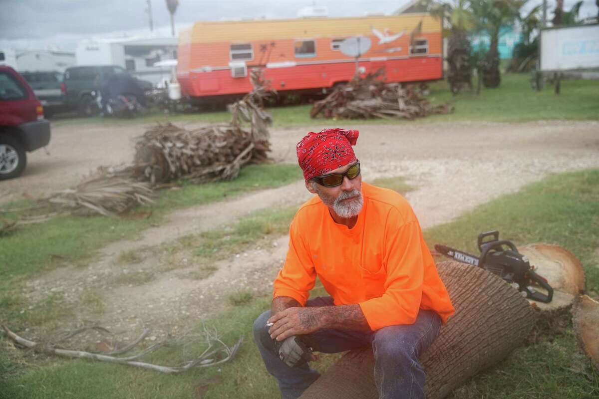 """Morris Womack takes a break while cutting down palm trees Tuesday, Sept. 14, 2021, in Surfside Beach. """"My trailer just rocked a little bit,"""" he said of Hurricane Nicholas' landfall earlier that morning."""