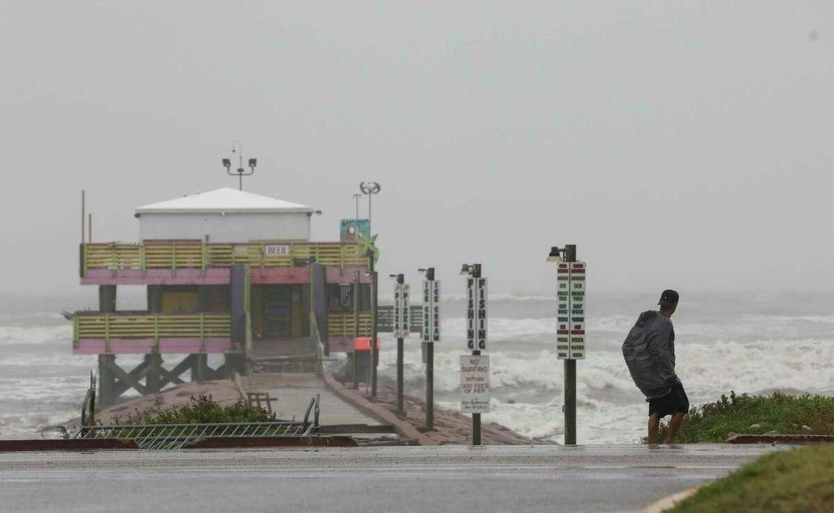 A man walks down Seawall Boulevard near 61st Street on Tuesday, Sept. 14, 2021, in Galveston, Texas. Hurricane Nicholas made landfall early in the morning along the coast.