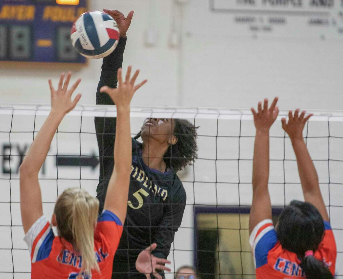 Midlabd High's Aniya Clinton goes for a kill as San Angelo Central's Morgan Strain and Alyssa Barron try to block 09/14/2021 at Midland High gym. Tim Fischer/Reporter-Telegram