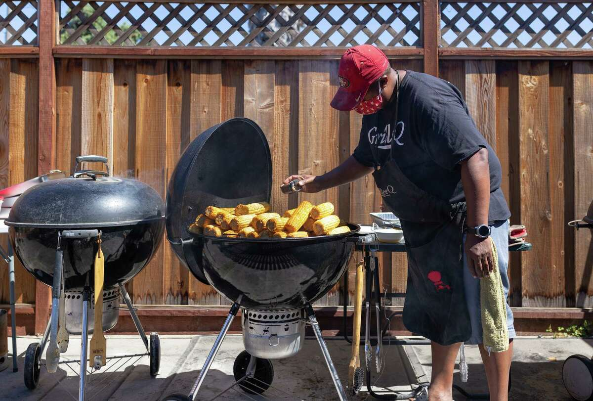 Lee Thomas, founder of GrilleeQ, seasons sweet yellow corn on one of his backyard grills. His home restaurant is the first of its kind to receive a permit from Alameda County's health department.