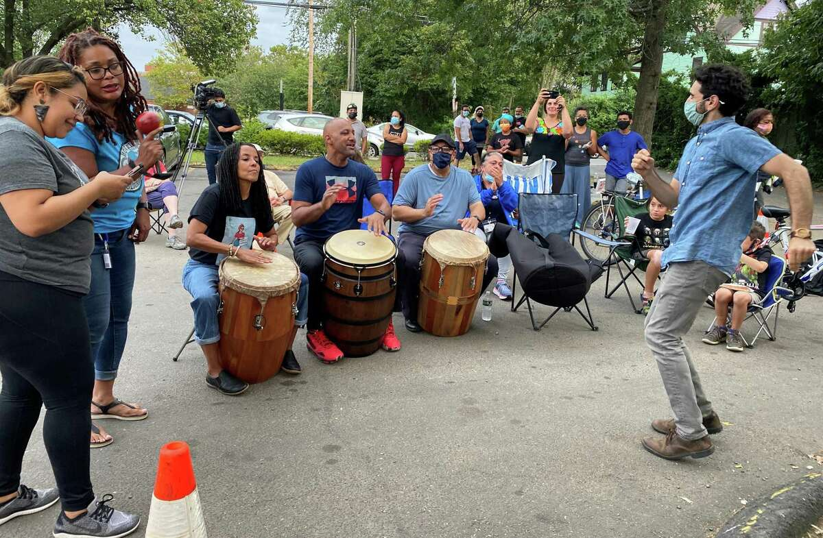 David Weintraub dances as Kica Maros, Alex Rosado and Kevin Diaz play the drums in New Haven's Fair Haven, where neighbors are working together to end violence.