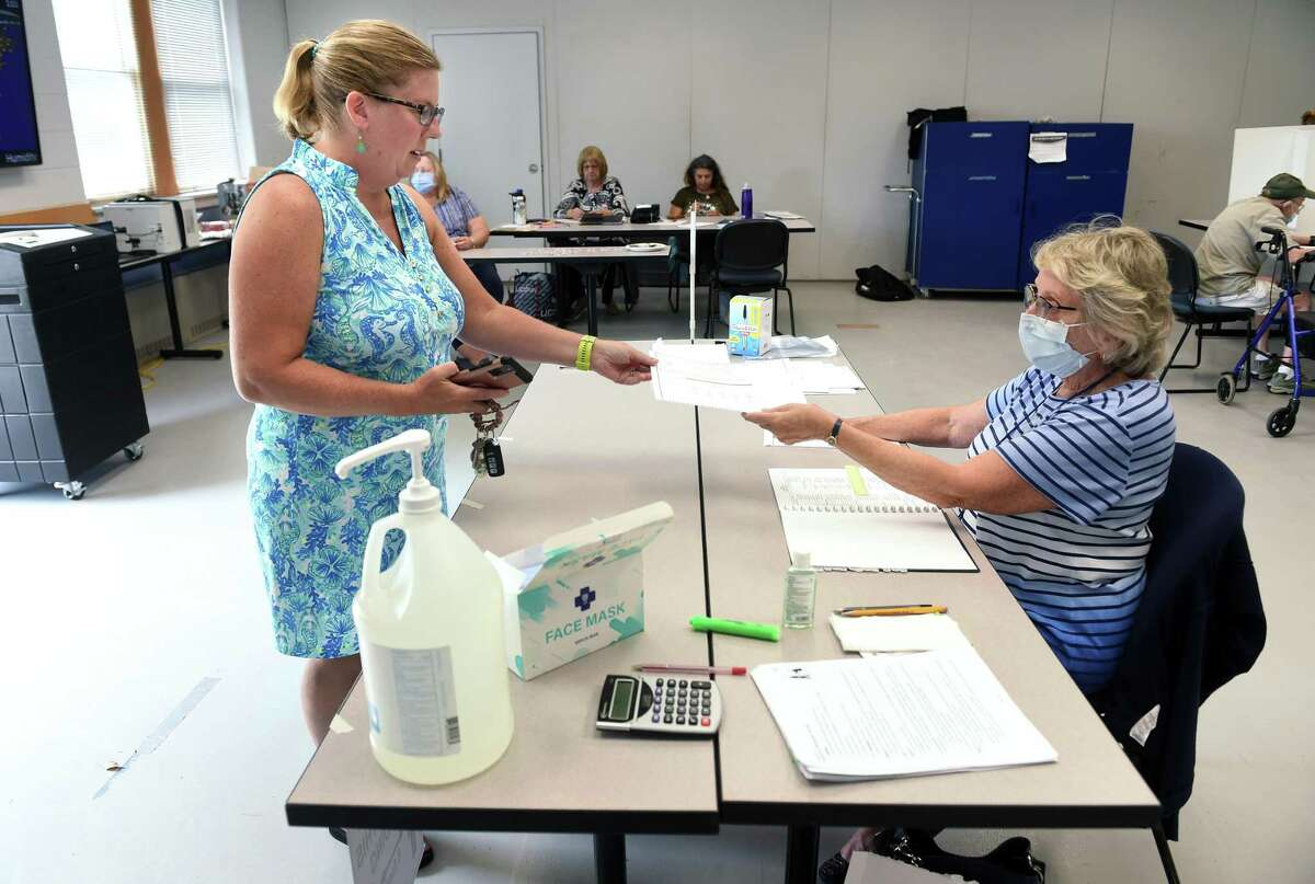 Julie Cusano, left, is handed a ballot from election official Carol Cipolla at the Guilford Fire Department where voting took place in the Republican primary for the Board of Education in Guilford. Cusano is the wife of candidate, Nick Cusano.