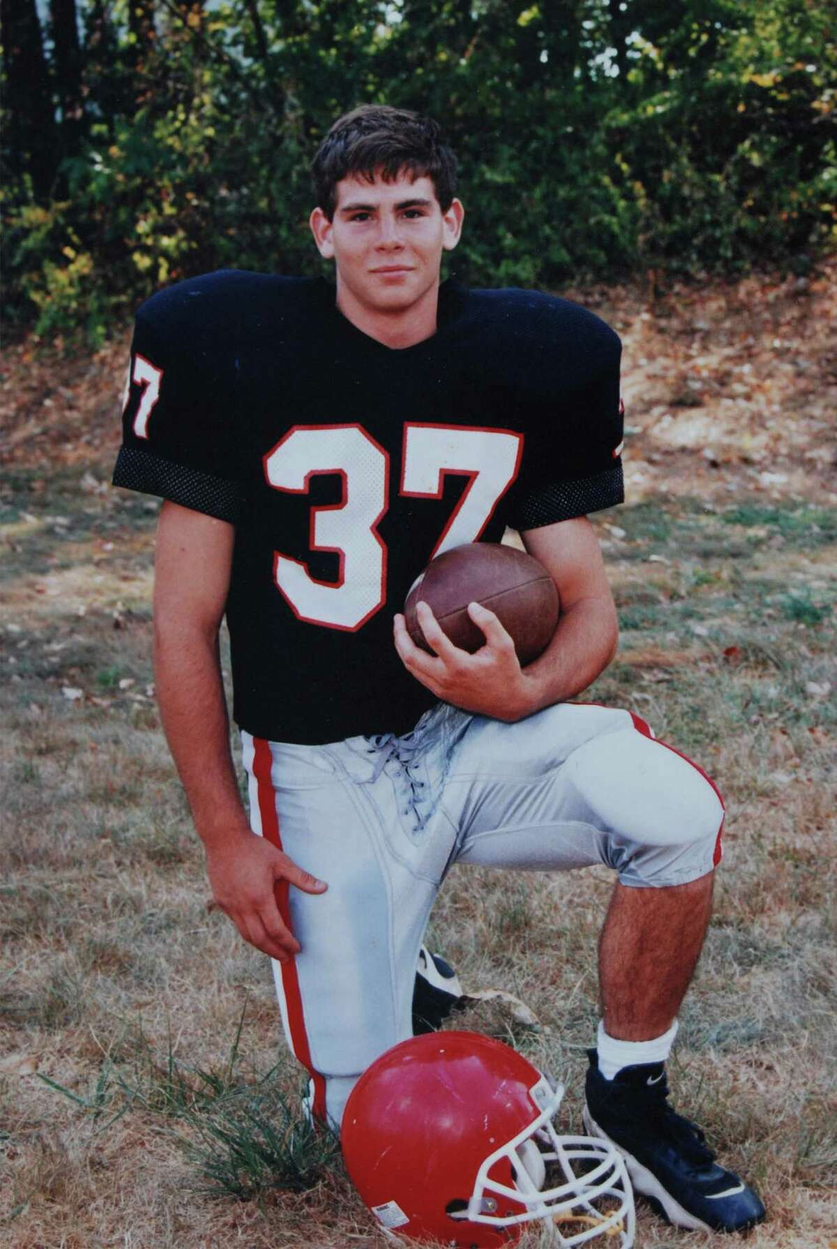 Brian Wilderman in his New Canaan High School football uniform. Wilderman, a captain of the Rams' 1997 team, died in 2000. New Canaan has renamed its first home game of the year the Brian Wilderman Game in his honor.