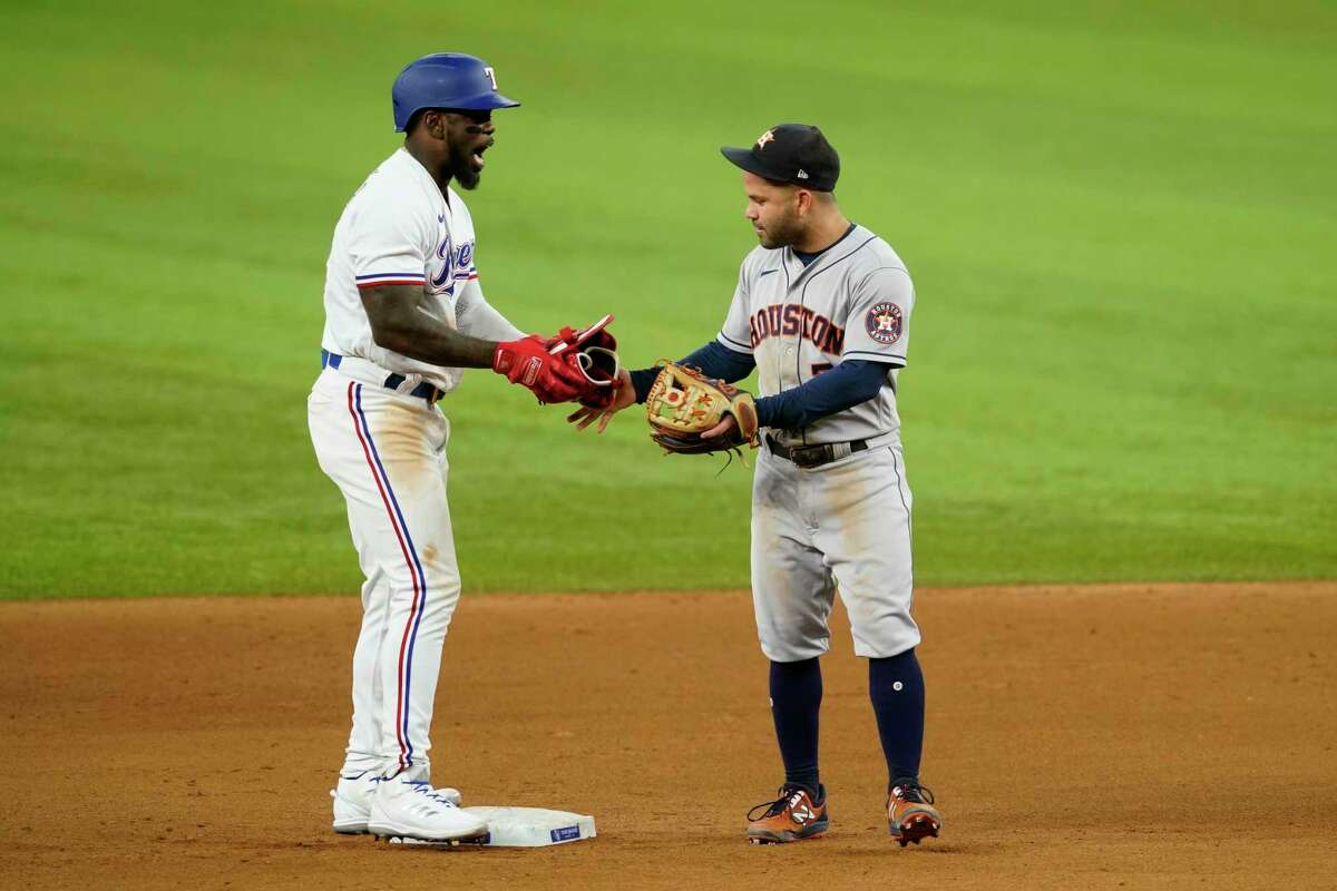 Texas Rangers' Adolis Garcia gives his batting equipment to Houston Astros second baseman Jose Altuve after hitting a double during the seventh inning of a baseball game in Arlington, Texas, Tuesday, Sept. 14, 2021. Altuve turned the equipment over to a bat boy. (AP Photo/Tony Gutierrez)
