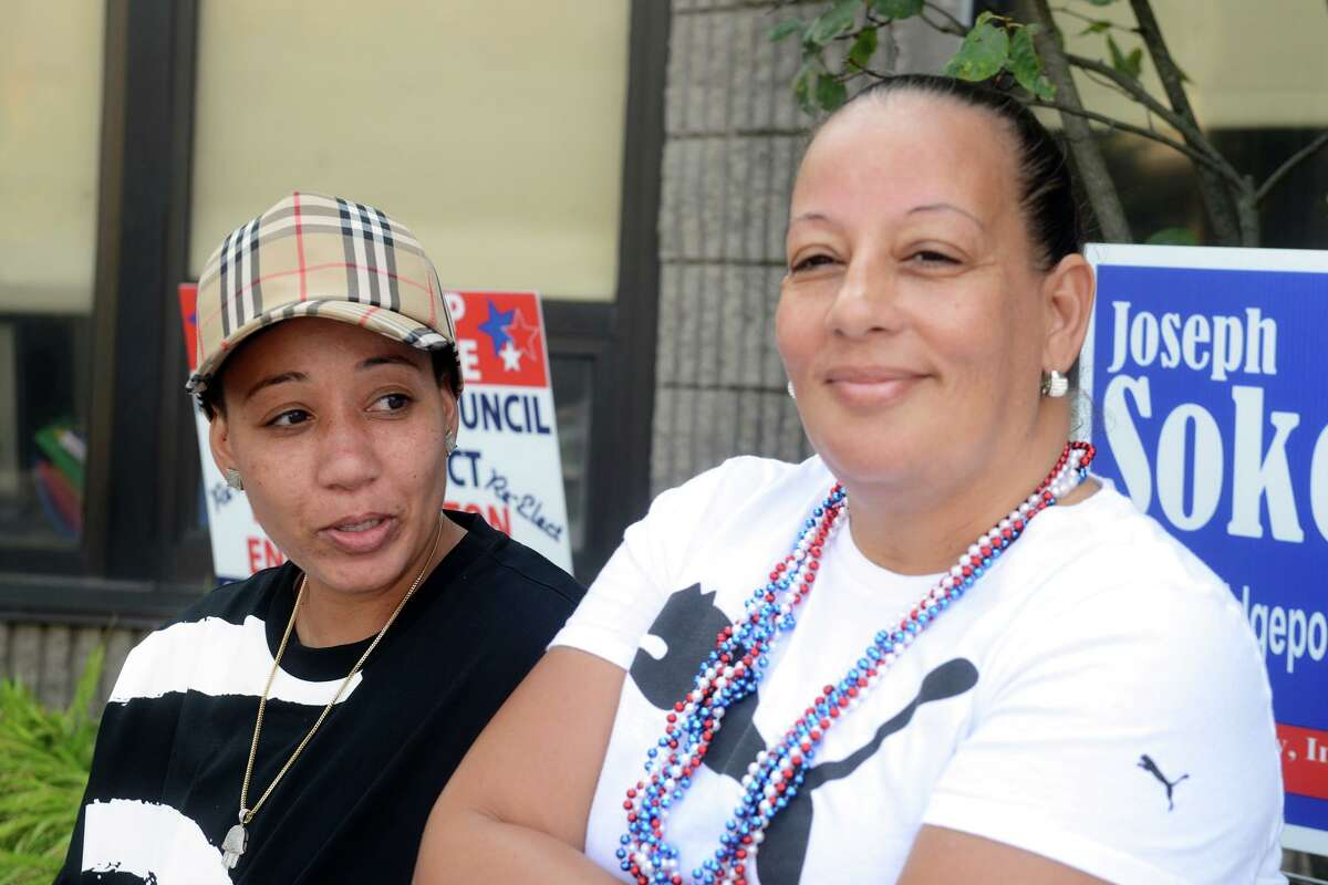 City Council member Eneida Martinez, right, sits with her daughter, Cecelia Cooper, outside Dunbar School, in Bridgeport, Conn. Sept. 14, 2021. Martinez seeks to continue representing the 139th district in Tuesday's Democratic primary.